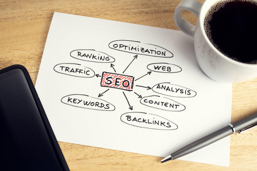 seo concept on paper under pen and coffee mug